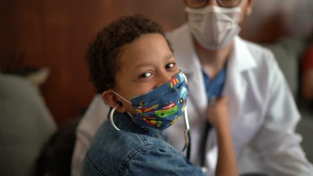 ハートビートを聞いている医師を調べている小さな男の子の肖像画 - 聴診器点の映像素材/bロール