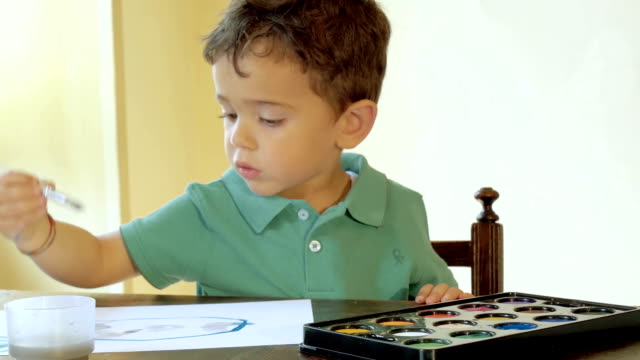 portrait of little boy painting with watercolors video