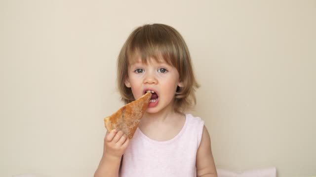 Portrait of little child girl bites off with big appetite piece of tasty pizza, eats and smiles