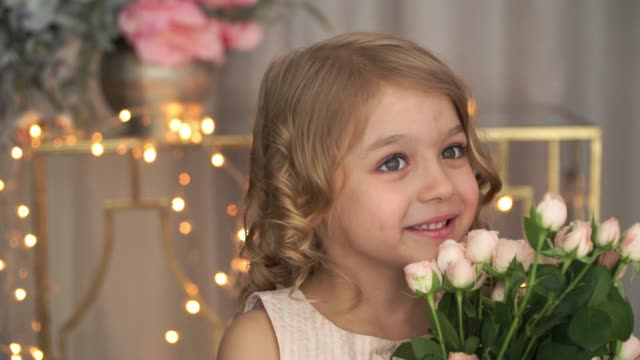 Portrait of little child girl looks at camera, smiles and smells pink roses flowers against background of golden blurred garland.