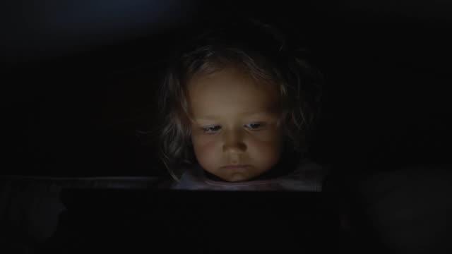 geceleri evde yatakta tablet teknolojisi kullanan küçük çocuk kız portresi. - dijital yerli stok videoları ve detay görüntü çekimi