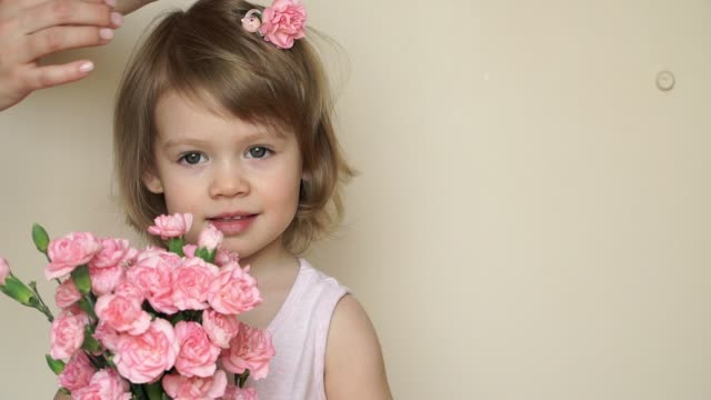 Portrait of little cute smiling girl stands and holds bouquet of pink carnations, mother's hands pins flower in daughter's hair, fixes and straightens hair.