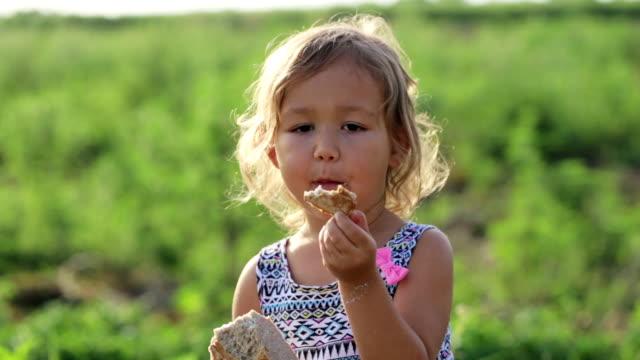 portrait of little girl eating homebaked bread on the field of organic eco farm - голодный стоковые видео и кадры b-roll
