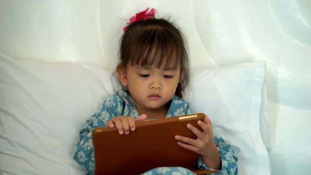 vídeos de stock, filmes e b-roll de retrato de menina olhando seu tablet - brasileiro pardo