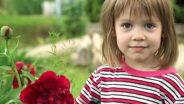 Portrait of little happy girl in summer park smells large bud of purple peony flower, looks at camera and smiles. Close-up.