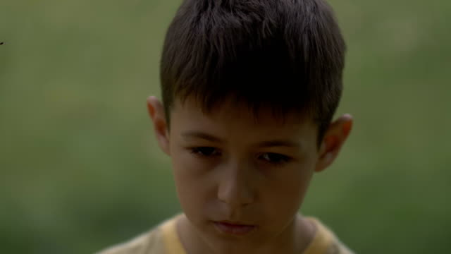 portrait of little sad desperate kid looking at camera, close up video