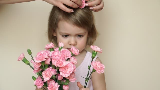 Portrait of little smiling girl stands and holds bouquet of pink carnations, mother's hands pins flower in daughter's hair. Mother's love and care