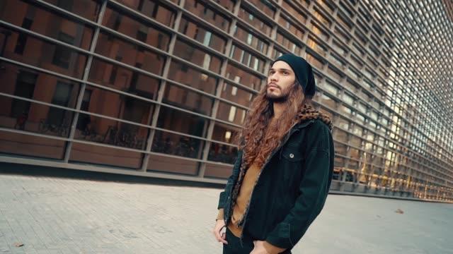 porträt von langhaarigen hipster zu fuß auf der straße in der modernen stadt - kopfbedeckung stock-videos und b-roll-filmmaterial