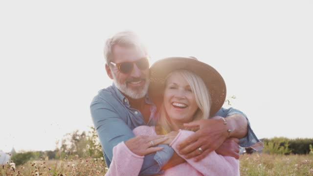 portrait of loving mature couple smiling into camera against flaring sun - зрелая пара стоковые видео и кадры b-roll