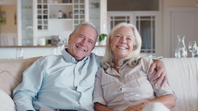 portrait of loving senior couple sitting with on sofa at home together - couple portrait caucasian video stock e b–roll