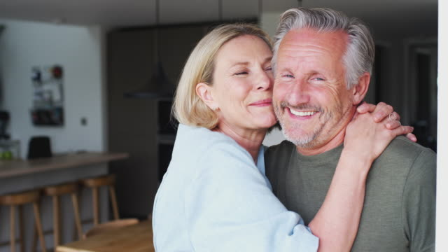 portrait of loving senior couple standing in kitchen together - couple portrait caucasian video stock e b–roll