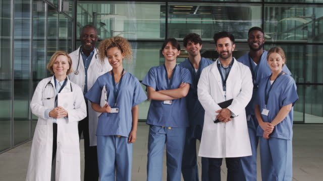 Portrait of male and female medical team standing in modern hospital building - shot in slow motion Portrait Of Medical Team Standing In Modern Hospital Building group of people stock videos & royalty-free footage