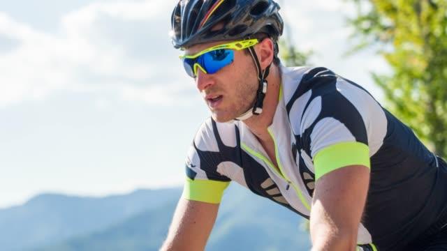 ritratto di atleta maschio in bicicletta su strada in una calda giornata di sole - occhiali protettivi video stock e b–roll