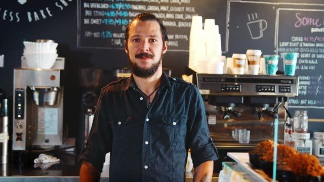 Portrait Of Male Barista Behind Counter In Coffee Shop Portrait Of Male Barista Behind Counter In Coffee Shop wait staff stock videos & royalty-free footage