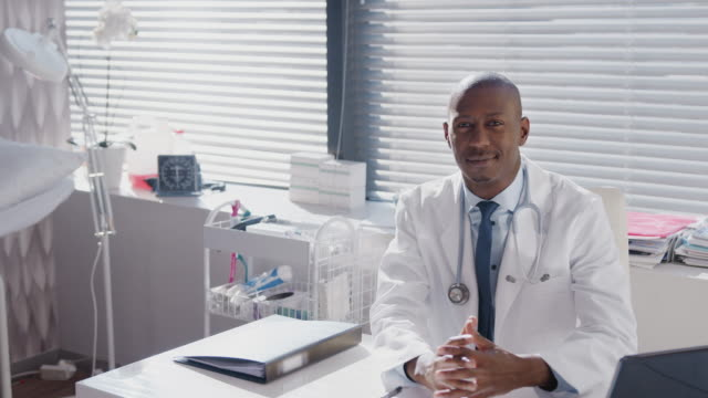 Portrait Of Male Doctor Wearing White Coat With Stethoscope Sitting At Desk In Office Portrait of male doctor wearing white coat and stethoscope around neck sitting behind desk and smiling at camera - shot in slow motion dermatology stock videos & royalty-free footage