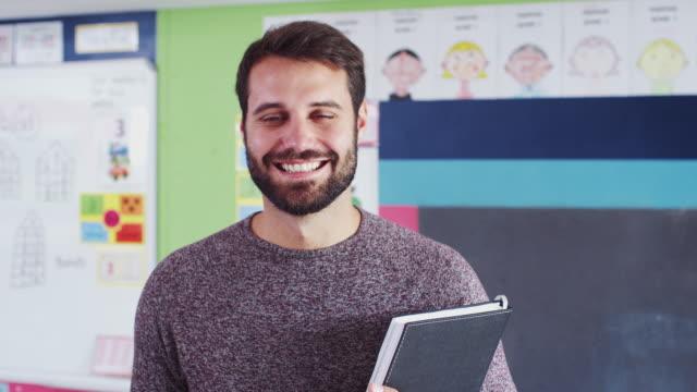 porträt eines männlichen grundschullehrers, der im klassenzimmer steht - lehrer stock-videos und b-roll-filmmaterial