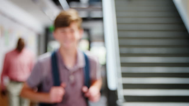 Portrait Of Male High School Student Standing By Stairs In College Building video