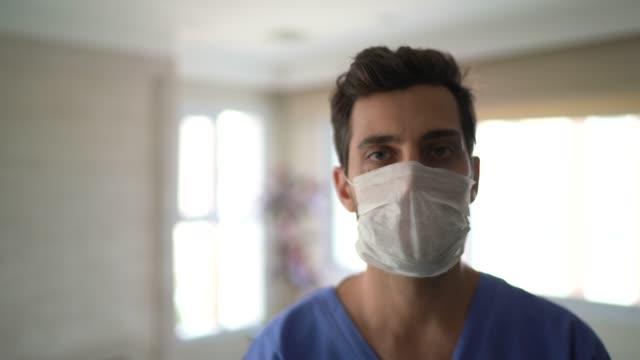 vidéos et rushes de verticale de l'infirmière mâle avec le masque de visage - infirmier