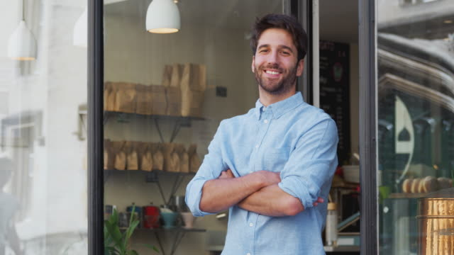 Portrait Of Male Owner Standing Outside Coffee Shop Portrait of male owner of coffee shop standing outside and smiling at camera - shot in slow motion independence stock videos & royalty-free footage