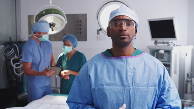 Portrait Of Male Surgeon Wearing Scrubs And Protective Glasses In Hospital Operating Theater video