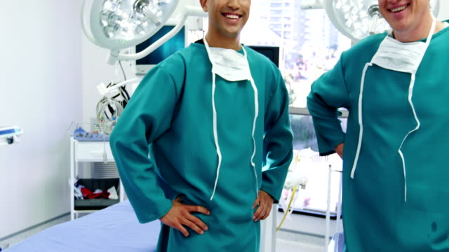 Portrait of male surgeons standing with hands on hips in operation room Portrait of male surgeons standing with hands on hips in operation room at the hospital arms akimbo stock videos & royalty-free footage