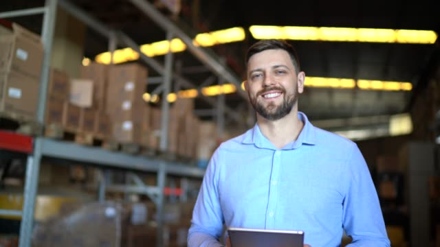 Portrait of male warehouse worker using digital tablet
