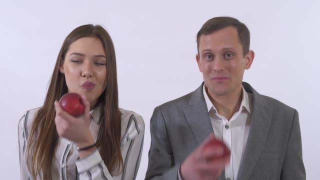 Retrato de hombre y mujer comer manzanas y sonrisa aislado sobre fondo blanco de cerca. - vídeo