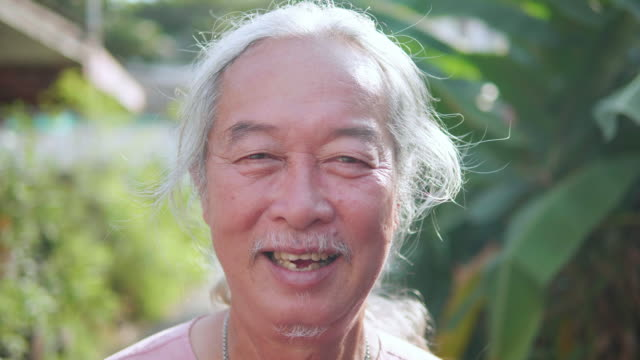 Portrait of Man in 60s , Asian senior man smiling. Elderly person looks at camera.