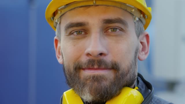 Portrait of Man in Safety Helmet and Earmuffs Close up face of bearded mature man in safety helmet taking off yellow earmuffs and looking at camera work helmet stock videos & royalty-free footage
