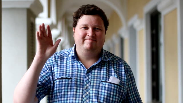 Portrait of man is waving hand and looking at camera. Face of a fat man wearing plaid shirt outdoor.
