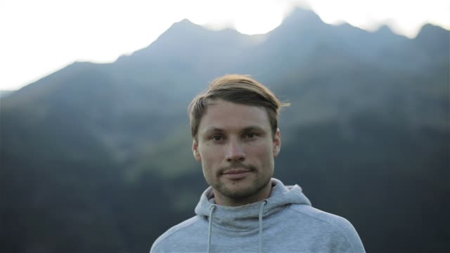 portrait of man looking at camera face close up outdoors in mountains morning nature. caucasian handsome confident calm 30s guy with loving kind brown eyes athlete sportsman traveler in grey sweater - coraggio video stock e b–roll
