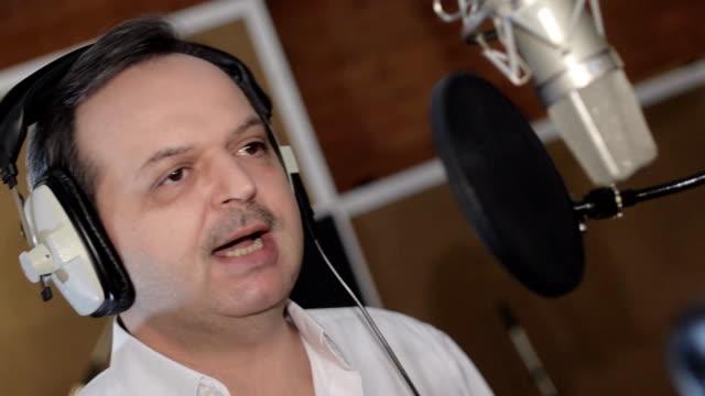 Portrait of man sing in headphones in front of microphone. Studio. Gesture video