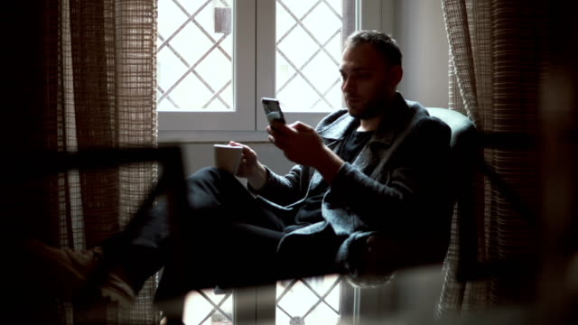 Portrait of man sitting in armchair in living room and using smartphone. Male browse the Internet and drinks coffee video