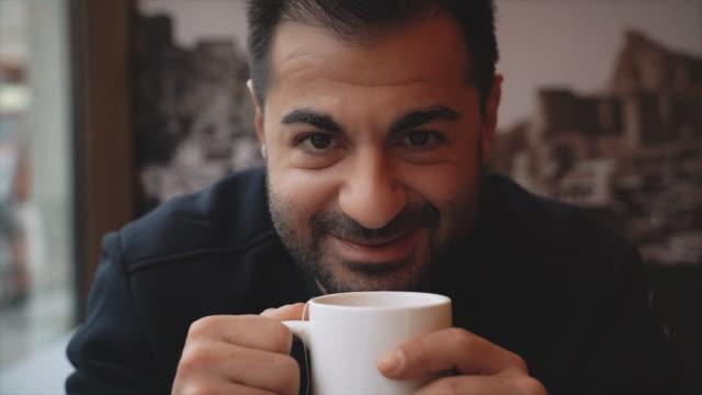 vídeos de stock, filmes e b-roll de retrato do homem que senta-se perto do indicador e que bebe o chá na cafetaria - café bebida