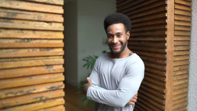 портрет человека, стоящего в дверях со скрещенными руками - бразилец парду стоковые видео и кадры b-roll