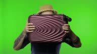 istock Portrait of man tourist hides behind a suitcase and looks out. Chroma key 1222119265