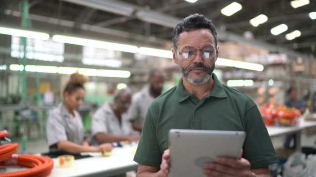 Portrait of man using tablet at industry Portrait of man using tablet and working in factory production line worker stock videos & royalty-free footage