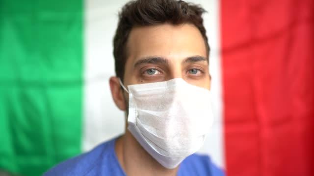 ritratto dell'uomo con maschera facciale e bandiera italiana sullo sfondo - lombardia video stock e b–roll