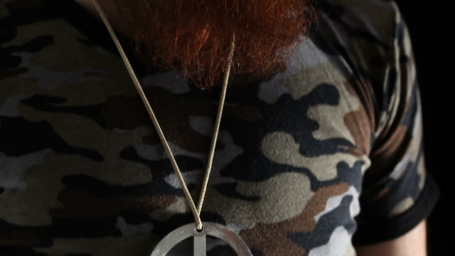 Portrait of man with long beard, large peace sign medal video