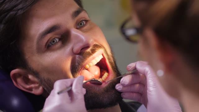 vídeos y material grabado en eventos de stock de retrato del hombre con la boca abierta en el consultorio dental - ortodoncista