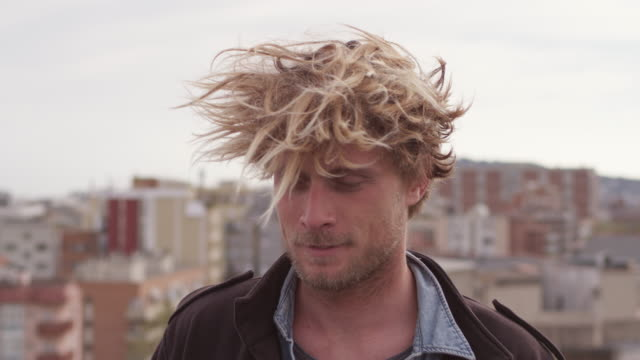 portrait of man with tousled hair against city - spettinato video stock e b–roll