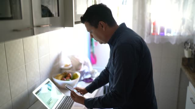 Portrait of man working using tablet and mobile phone at home Portrait of man working using tablet and mobile phone at home financial planning stock videos & royalty-free footage
