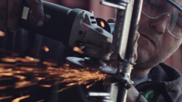 portrait of man works with grinder in his garage - stock video - narzędzie z napędem elektrycznym filmów i materiałów b-roll