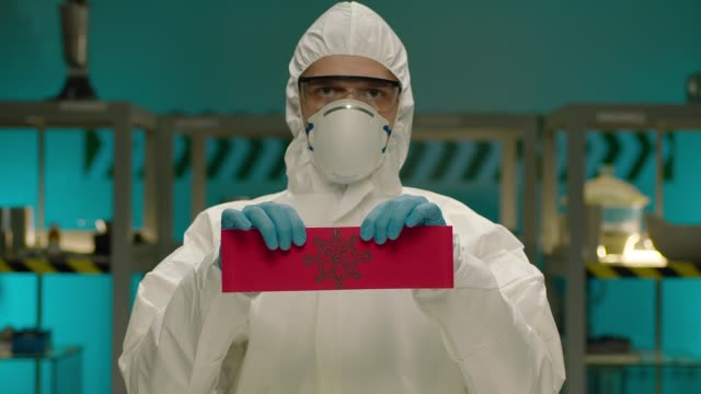 Porträt des maskierten Arbeiters . Konzept der Coronavirus-Quarantäne. MERS-Cov. Neuartiges Coronavirus. Arzt mit einer Allgemeinen Sicherheitsuniform Zerreißt das rote Papier mit dem Wort Coronavirus. COVID-2019 oder nCoV2019 – Video