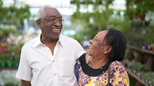 portrait of mature african couple customer at flower market - coppia anziana video stock e b–roll