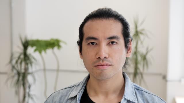 porträtt av mogen asiatisk man, ändra känslor från allvarliga till leende - mellan 30 och 40 bildbanksvideor och videomaterial från bakom kulisserna