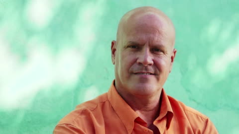 Portrait of mature bald man smiling at camera Portrait of mature caucasian man with orange shirt sitting in park and looking at camera with happy expression. 5 of 11 medium shot stock videos & royalty-free footage