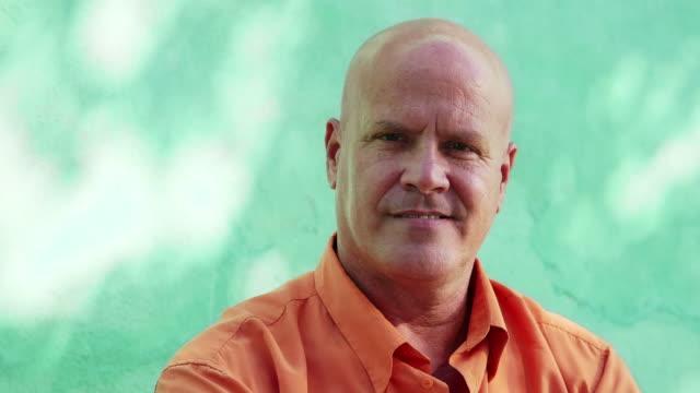 portrait of mature bald man smiling at camera - halvbild bildbanksvideor och videomaterial från bakom kulisserna