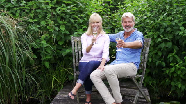 Portrait Of Mature  Couple Celebrating With Champagne Sitting On Chairs On Jetty By Lake