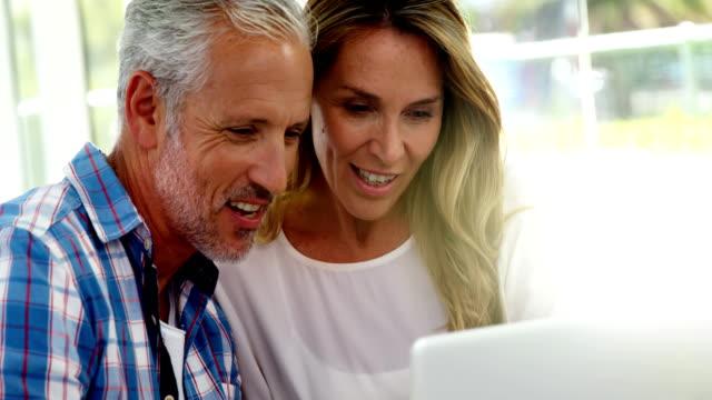 vidéos et rushes de portrait de couple mature cherche un ordinateur portable - image